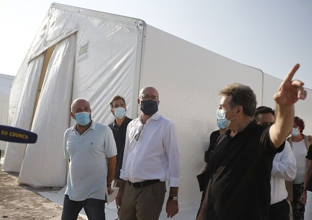 European Council President Charles Michel, center, is accompanied by Greek Minister of Citizen Protection Michalis Chrisochoidis visits the new temporary refugee camp in Kara Tepe on the northeastern island of Lesbos, Greece, Tuesday, Sept. 15, 2020.