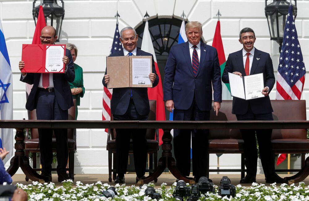 Netanyahu, Abdullah bin Zayed el Nahyan ve  Abdullatif bin Raşid ez Zayani, imzalanan anlaşmanın İngilizce, İbranice ve Arapça nüshalarını gösteriyor