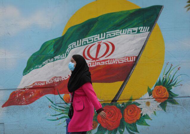 Tahran'da İran bayraklı duvar resminin önünden geçen maskeli kadın