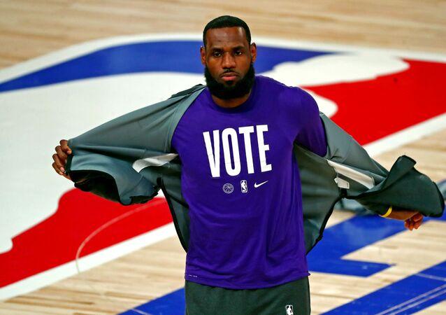 NBA finali 5. maçı için ısınmaya çıkan Los Angeles Lakers yıldızı LeBron James, oy kullanılması çağrısı yapan tişörtünü gösterirken