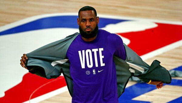 NBA finali 5. maçı için ısınmaya çıkan Los Angeles Lakers yıldızı LeBron James, oy kullanılması çağrısı yapan tişörtünü gösterirken - Sputnik Türkiye