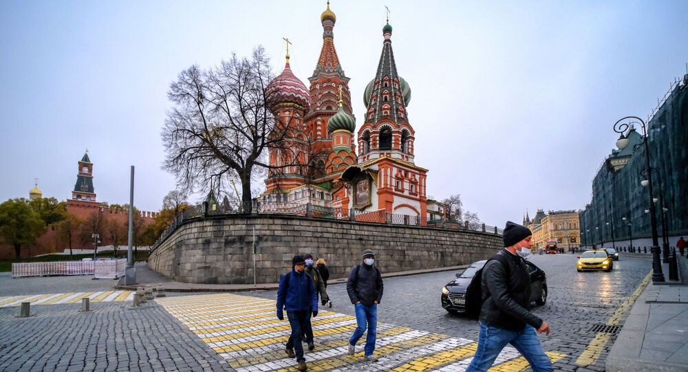 Men wearing face masks to protect against the coronavirus disease walk in front of St. Basil's cathedral in downtown Moscow on November 2, 2020. (Photo by Yuri KADOBNOV / AFP)
