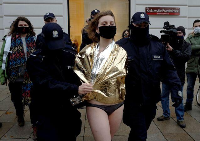 Polonya'da Anayasa Mahkemesi'nin kürtaj yasağı kararını Cumhurbaşkanlığı Sarayı önünde soyunarak protesto eden biri erkek iki sanatçıdan Ania Bielawska, polis tarafından götürülürken