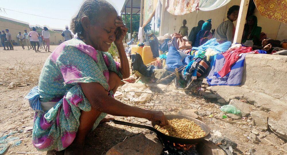 Etiyopya'nın Tigray bölgesindeki çatışmalardan kaçan binlerce kişinin sığındığı Sudan'ın Hamdait köyünde yemek pişirmeye çalışan sığınmacı bir kadın