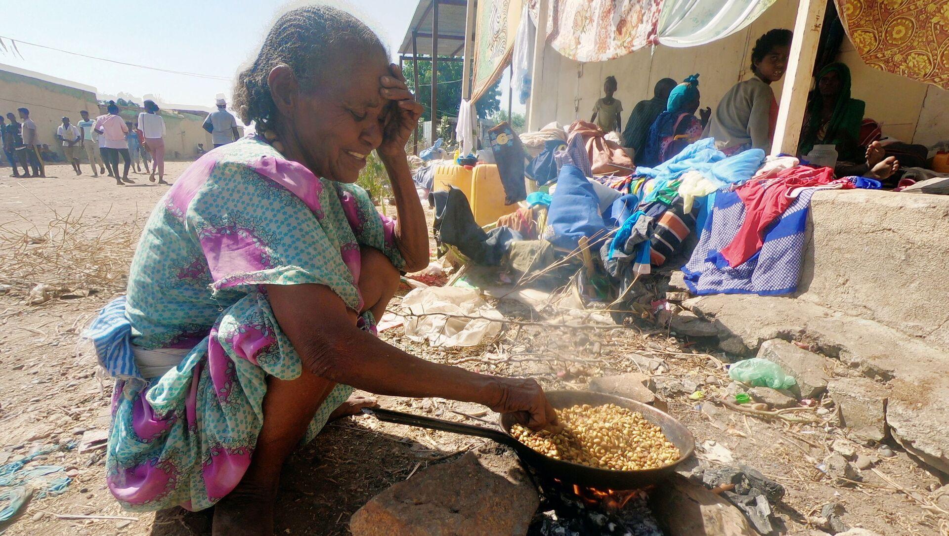 Etiyopya'nın Tigray bölgesindeki çatışmalardan kaçan binlerce kişinin sığındığı Sudan'ın Hamdait köyünde yemek pişirmeye çalışan sığınmacı bir kadın - Sputnik Türkiye, 1920, 28.07.2021