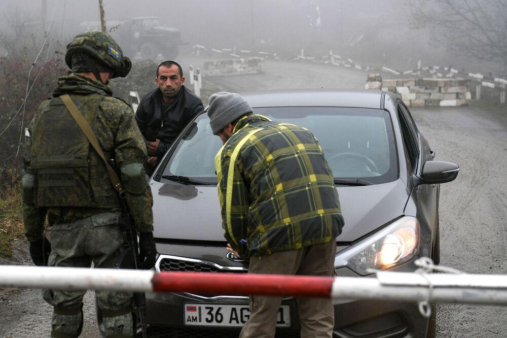 Rus barış gücü görevlisi, Dağlık Karabağ'ı Ermenistan'a bağlayan Laçin koridorundaki güvenlik kontrol noktasında sivil aracı kontrol ederken