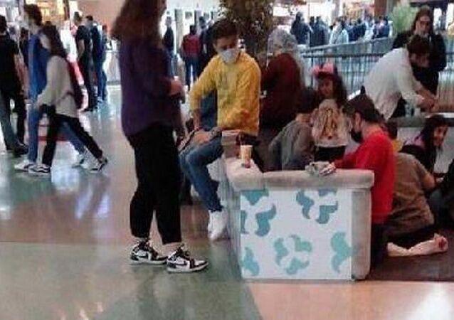 İzmir'de, yeni tip koronavirüs (Kovid-19) tedbirleri kapsamında, masa ve sandalyelerin kaldırıldığı alışveriş merkezindeki yemek katında restoranlardan yiyecek alanlar, yere oturarak yedi.