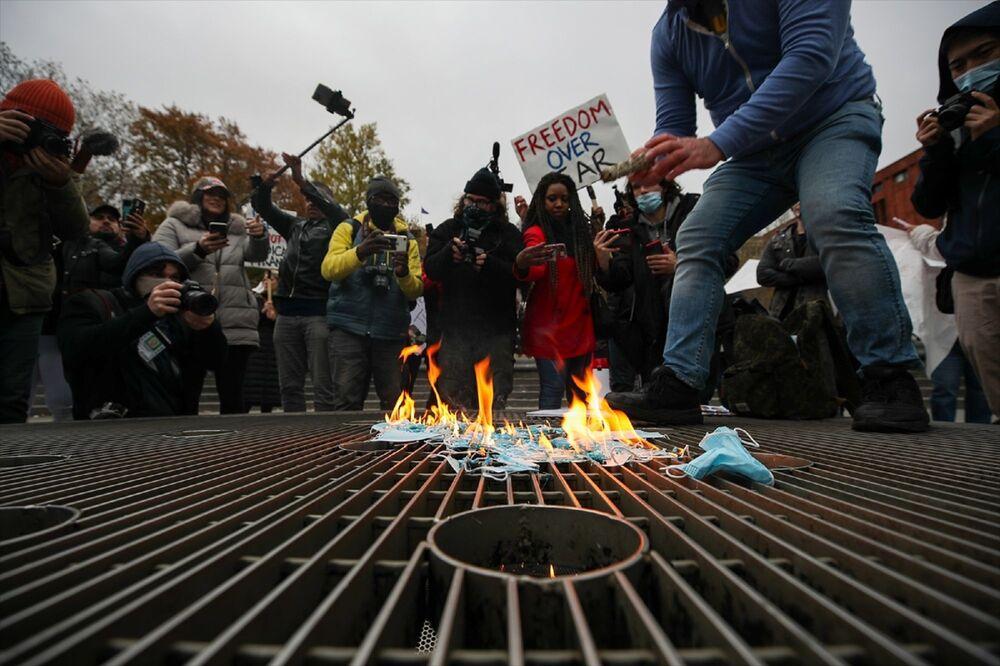Maskeye hayır ve maskeleri yak şeklinde slogan atan göstericiler, yanlarında getirdikleri maskeleri ateşe verdi.