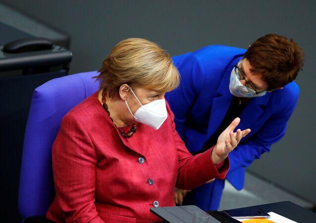 Almanya parlamentosunda Başbakan Angela Merkel, Savunma Bakanı Annegret Kramp-Karrenbauer ile konuşurken