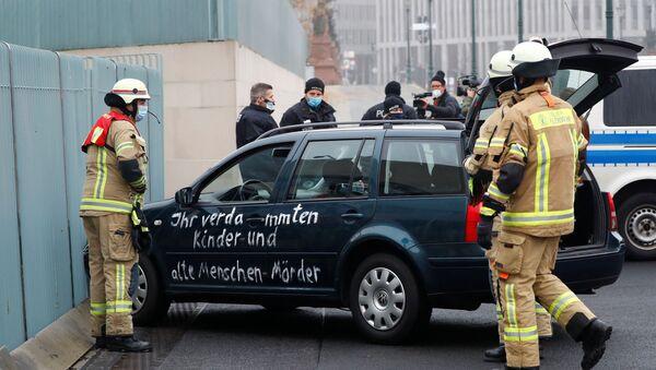Almanya'nın başkenti Berlin'de Angela Merkel'in ofisinin bulunduğu başbakanlık binasının dış kapısına çarpan ve üzerinde sloganlar yazılı bulunan araba - Sputnik Türkiye