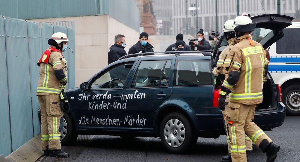 Almanya'nın başkenti Berlin'de Angela Merkel'in ofisinin bulunduğu başbakanlık binasının dış kapısına çarpan ve üzerinde sloganlar yazılı bulunan araba