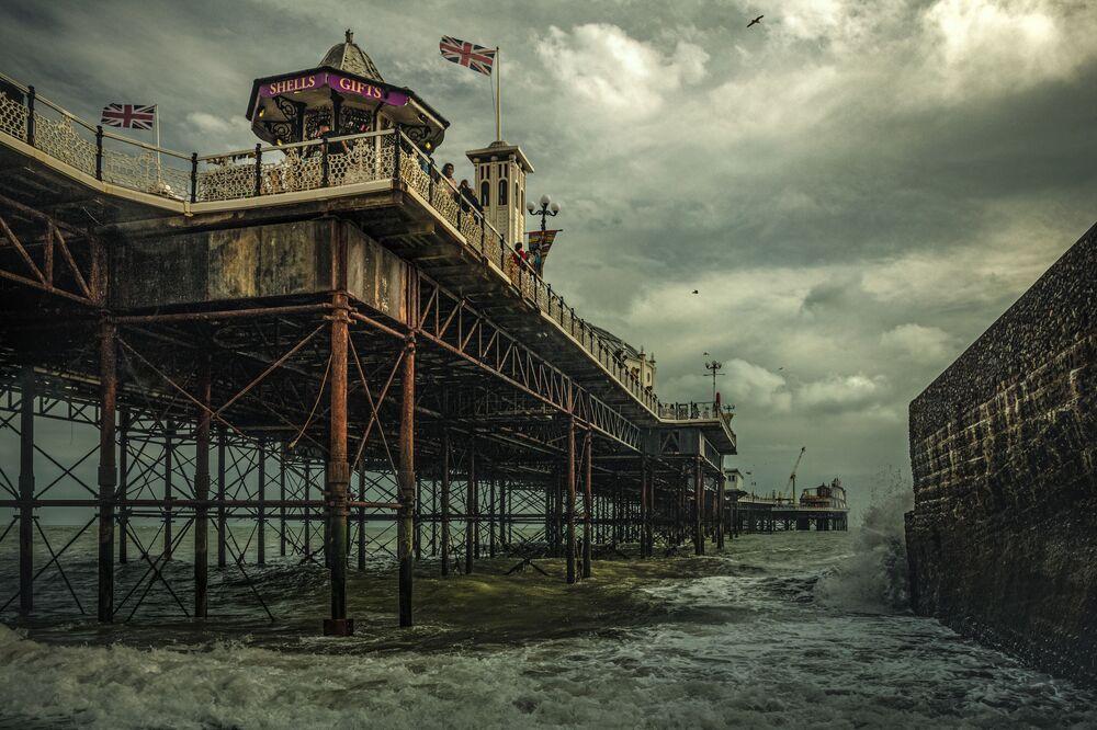 2020 Tarihi Mekanlar Fotoğrafçılık Yarışması'nın Baş Ödülü'nü kazanan fotoğrafçı Michael Marsh'ın  çektiği İngiltere'deki Brighton İskelesi görüntüsü.  Brighton Pier olarak bilinen 525 m uzunluğundaki iskele şimdiye dek inşa edilmiş en iyi iskele olarak tarihe geçti. 1891 yılında açılan iskele tiyatro ve konser salonları, lokantaları ve okuma salonları ile popülerliğini 1938'e kadar sürdürdü. Savaş yıllarında geçici olarak kapatılan iskele, savaştan sonra faaliyetine devam etse de 1975 yılındaki güçlü fırtınada büyük zarar gördü. 1984'te yeni sahibi tarafından restorasyonu yapılan Brighton Pier günümüzde lokanta ve dükkanları, oyun salonları ve uç kısmındaki lunaparkıyla hala popüler.