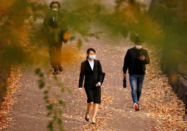 Japonya'nın başkenti Tokyo'da maske takmış halde güz yaprakları arasından yürüyerek işe gidenler
