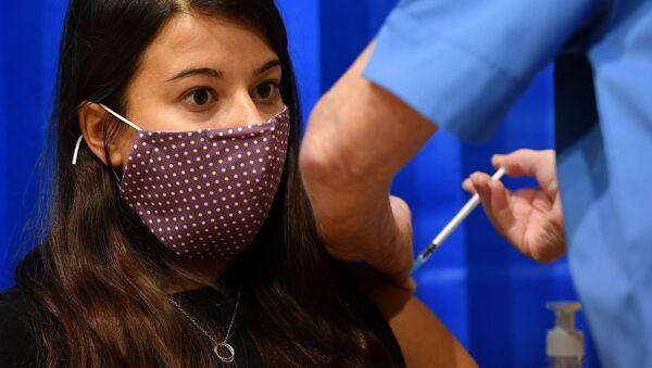 Kovid-19 pandemisi nedeniyle Britanya'nın en büyük aşı programı hayata geçti: İlk günde Galler bölgesinin Cardiff kentinde BioNTech-Pfizer aşısı yapılan bir kadın - Sputnik Türkiye