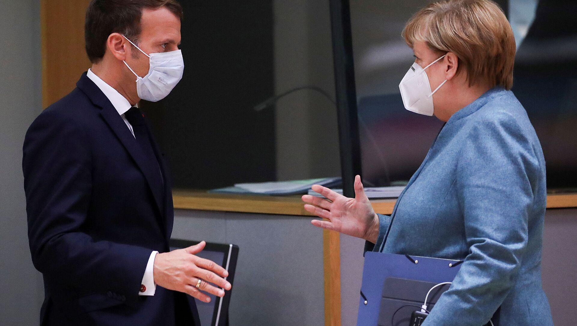 Fransa Cumhurbaşkanı Emmanuel Macron ile Almanya Başbakanı Angela Merkel, 15 Ekim 2020'deki AB zirvesinde tokalaşırken - Sputnik Türkiye, 1920, 05.08.2021
