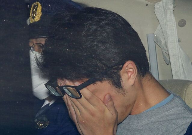 Japonya başkenti Tokyo'da polis aracında götürülürken yüzünü kapatan 'Twitter katili' Takahiro Shiraishi (Şiraişi)