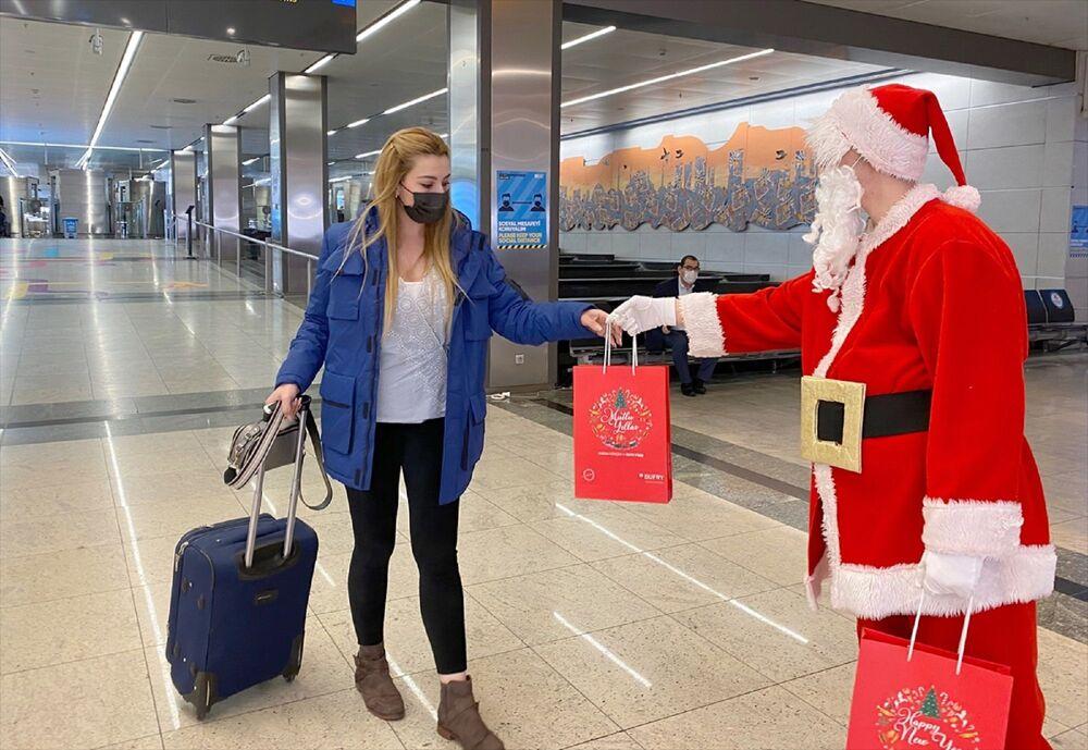 Noel baba kostümlü animatör, gelen yolculara mutlu yıllar dileyerek hediye paketleri takdim etti.