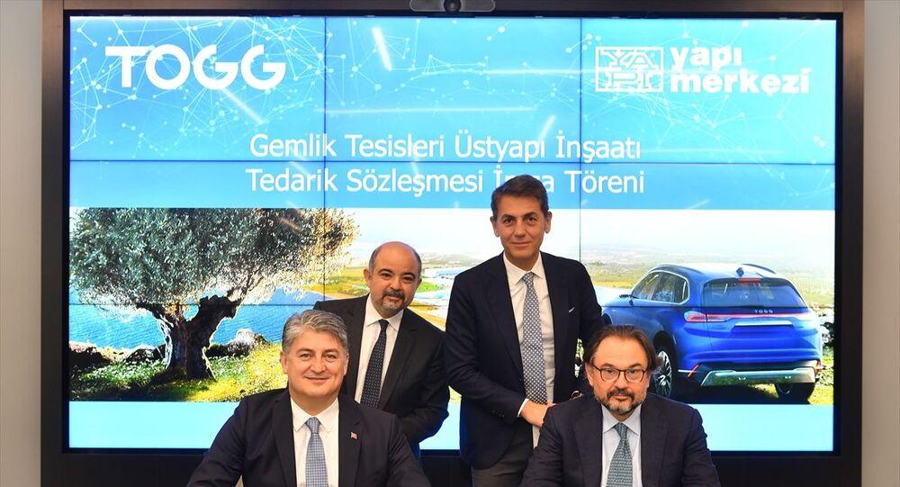 Türkiye'nin Otomobili Girişim Grubu'nun (TOGG) Bir Fabrikadan Daha Fazlası olarak tanımlanan Gemlik tesisinin üstyapı inşaatını Yapı Merkezi gerçekleştirecek. İmza törenine, TOGG Üst Yöneticisi (CEO) Gürcan Karakaş (ön solda) ile Yapı Merkezi İnşaat ve Sanayi AŞ Yönetim Kurulu Başkanı Başar Arıoğlu (ön sağda) katıldı.