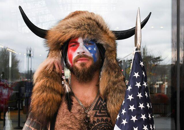 ABD Kongresi'ne saldıran Donald Trump yandaşları arasından üstü çıplak, yüzü ABD bayrağına boyanmış halde kürklü-boynuzlu şapkasıyla öne çıkanJake Angeli, namı diğer 'QAnon şamanı'