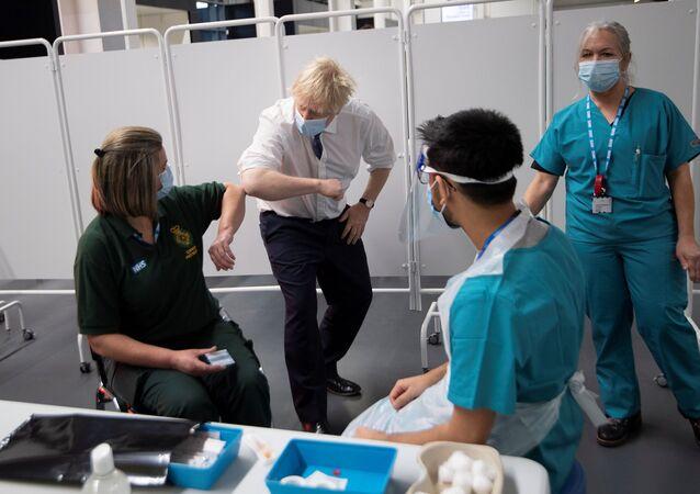 Bristol'de bir stadyumdan dönüştürülen toplu aşılama merkezini ziyaret eden Başbakan Boris Johnson, sağlık çalışanlarına dirsek selamı verirken