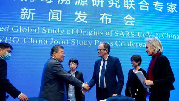 Çin'in Vuhan kentinde yeni tip koronavirüsün kaynağını araştıran Dünya Sağlık Örgütü (DSÖ) ekibi, elde ettiği bulgularla ilgili basın toplantısı düzenledi. Ekibin lideri Peter Ben Embarek, Marion Koopmans'ın eşliğinde, Çinli uzman Liang Wannian ile el sıkışırken... - Sputnik Türkiye