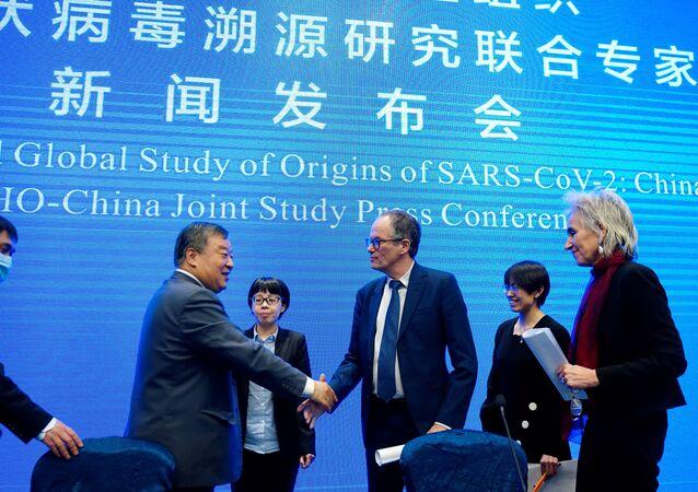 Çin'in Vuhan kentinde yeni tip koronavirüsün kaynağını araştıran Dünya Sağlık Örgütü (DSÖ) ekibi, elde ettiği bulgularla ilgili basın toplantısı düzenledi. Ekibin lideri Peter Ben Embarek, Marion Koopmans'ın eşliğinde, Çinli uzman Liang Wannian ile el sıkışırken...