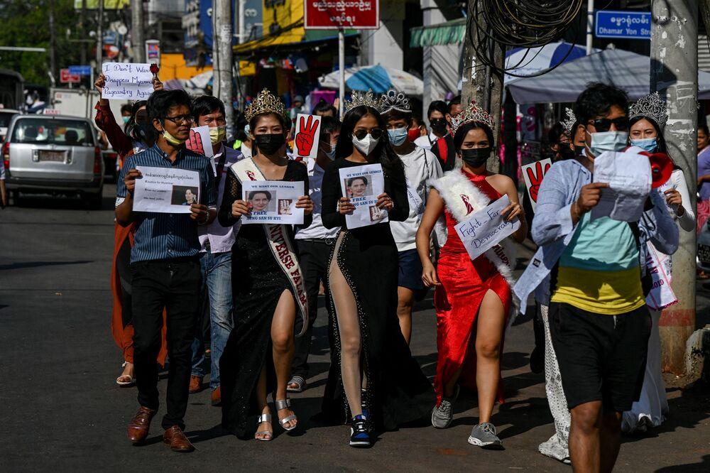 Bazı kadınlar da güzellik yarışmasına katılır tarzda giyindi, gözaltındaki Dışişleri Bakanı ve ülkenin fiili lideri Aung San Suu Çii'nin fotoğraflarını taşıdı.