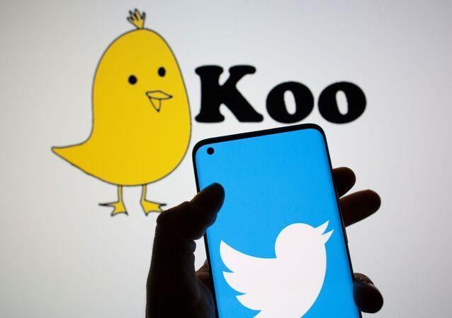 Koo uygulamasının posteri önünde tutulan cep telefonunda Twitter logosu