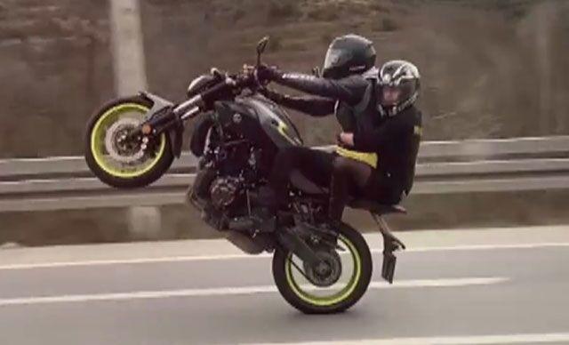 Arkasında oturan kişiyle trafikte tek teker üzerinde giden motosiklet sürücüsüne ceza
