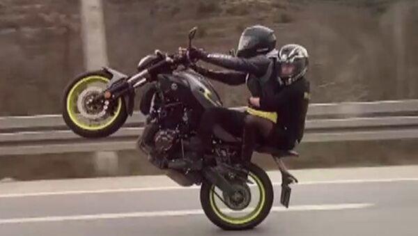 Arkasında oturan kişiyle trafikte tek teker üzerinde giden motosiklet sürücüsüne ceza - Sputnik Türkiye