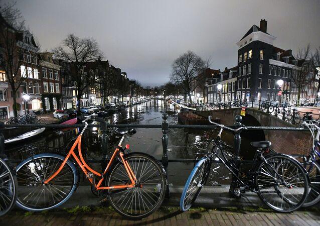 Gece kanal üzerindeki köprüye park edilen bisikletler,  Amsterdam, Hollanda