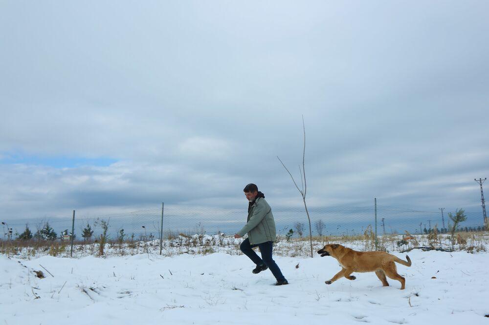 Çiftçi, işten sonra köpeğiyle oynuyor.