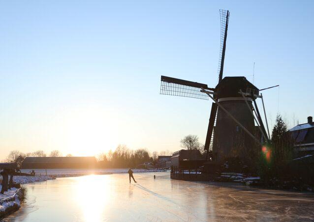 Değirmenleriyle meşhur Hollanda'nın Molenaarsgraaf bölgesinde kışın tutan buzlarda paten yapan bir erkek