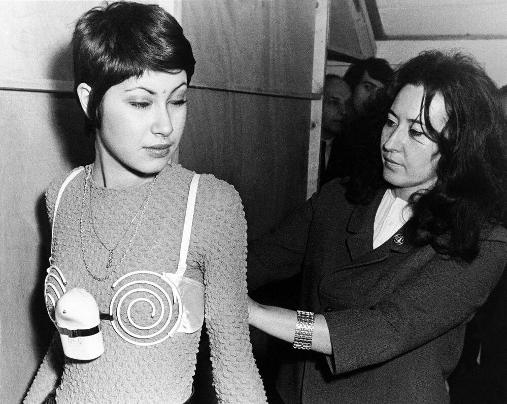 Bir model, 1970'li yıllarda Belçika'da kadın göğüs kaslarının güçlendirilmesi için icat edilen spiral elektrikli sütyeni tanıtırken, 13.03.1971