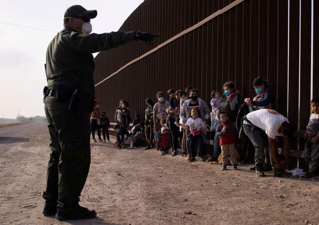 Meksika'dan tekneyle Rio Grande nehrini geçerek ABD sınırına varan göçmenleri duvar önünde sıraya dizen ABD'li federal sınır koruma ajanları (Penitas, Teksas)
