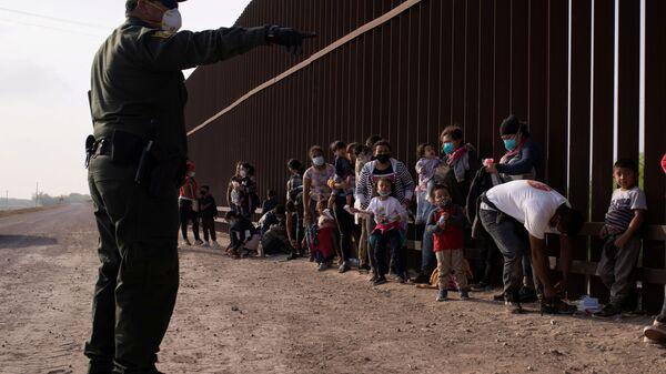 Meksika'dan tekneyle Rio Grande nehrini geçerek ABD sınırına varan göçmenleri duvar önünde sıraya dizen ABD'li federal sınır koruma ajanları (Penitas, Teksas) - Sputnik Türkiye