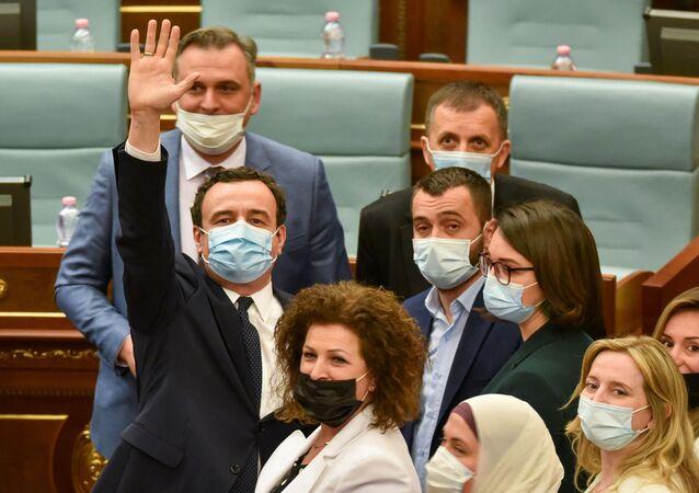 Kosova meclisinde yeniden başbakan seçilen Albin Kurti yemin ettikten sonra el sallarken