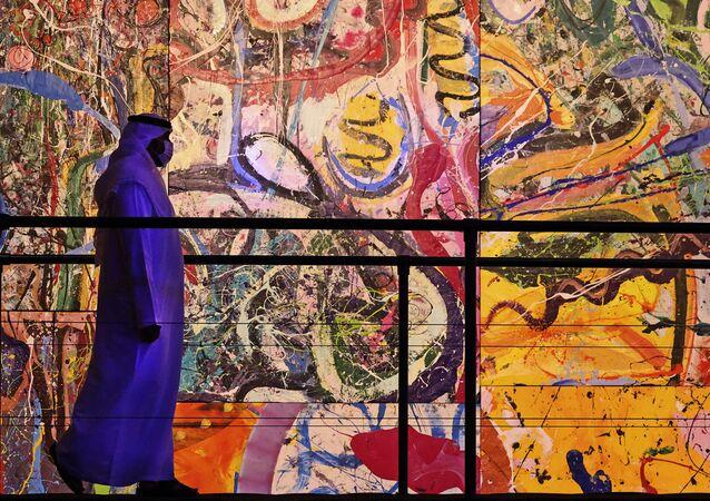 Sacha Jafri'nin 'The Journey of Humanity' (İnsanlığın Yolculuğu) isimli tablosunun önünden geçen bir ziyaretçi (BAE, Dubai, Otel Atlantis, The Palm)