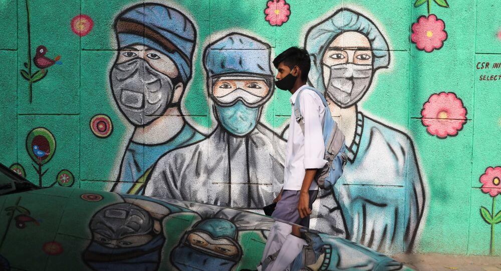 Hindistan başkenti Yeni Delhi'de insanlar, koronavirüs pandemisiyle mücadele eden sağlık çalışanlarının resmedildiği graffitinin önünden geçerken