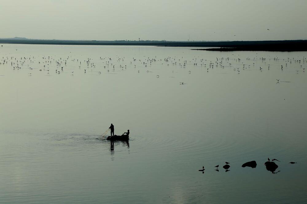 Baraj gölü üzerinde teknelerinde balık avlayan balıkçılar ve uçuşan martılar tabloluk görüntüler oluşturuyor.