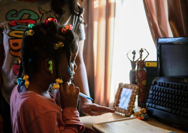 ABD'nin Kentucky eyaletinin Louisville kentinde uzaktan eğitim alan çocuk ile ona yardım eden velisi