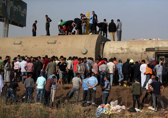 Mısır'da bu kez Kalyubiye vilayetinde bir yolcu treni raydan çıkarak devrildi. Olay yerinde toplananlar devrilen vagonların üzerine çıktı.