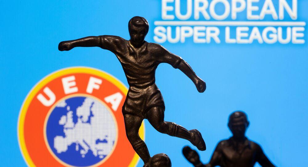 UEFA ve Avrupa Süper Ligi logoları önünde futbolcu bibloları