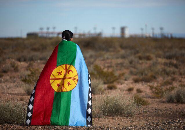 Dev şirketlerin Arjantin'deki Vaca Muerta'da 30 bin kilometrekarelik alanda kaya petrolü ve gazı çıkardığı toprakların kendilerine ait olduğunu söyleyen yerli Mapuçe halkının sözcüsü Lorena Bravo, gaz tesisi önünde Mapuçe bayrağına sarınmış halde