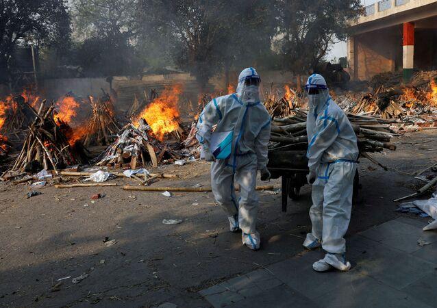Hindistan başkenti Yeni Delhi'de Kovid-19 kurbanlarının yakıldığı krematoryuma odun taşıyan koruma kıyafetli sağlık çalışanları