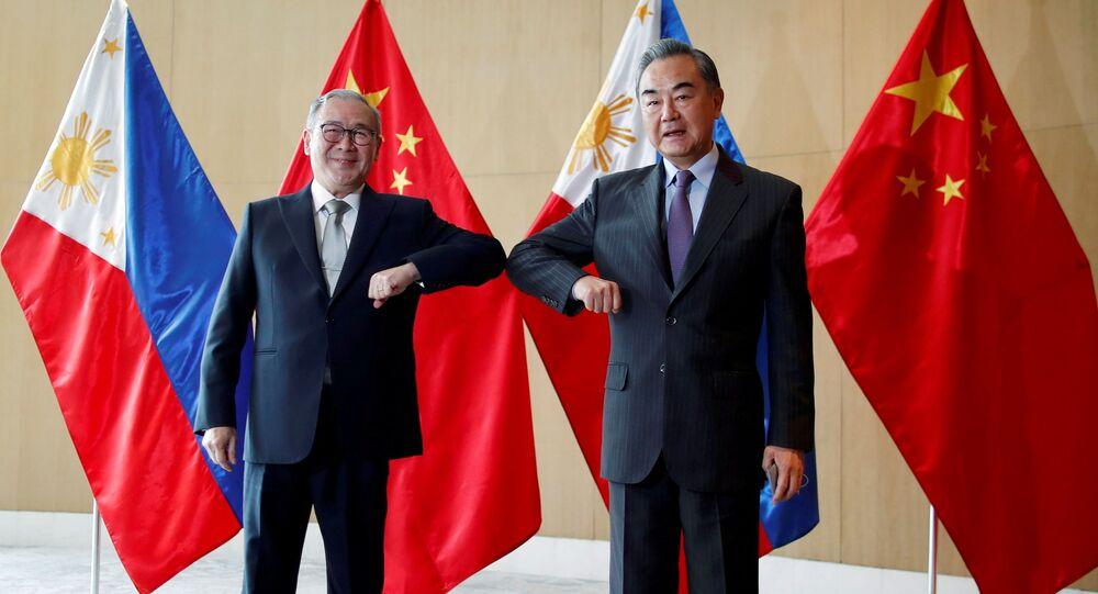 Filipinler Dışişleri Bakanı Teodoro Locsin ile Çin Dışişleri Bakanı Wang Yi, Manila'daki görüşmede dirsek selamı verirken