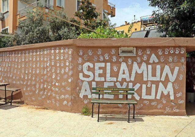 """Antalya'da bir genç, boya kovasına batırdığı ellerinin iziyle caminin bahçe duvarlarına 'selamlama' motifleri yaptı. İmam gençten şikayetçi olurken genç ise, """"Kimse birbirine selam vermiyordu"""" diyerek kendini savundu."""