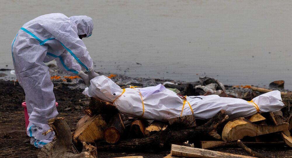 Kovid-19'dan ölen yakınıyla Ganj Nehri kıyısında yakılmasından önce koruyucu kıyafetler giyerek vedalaşan Hindistanlı (Uttar Pradeş, Garhmukteshwar)