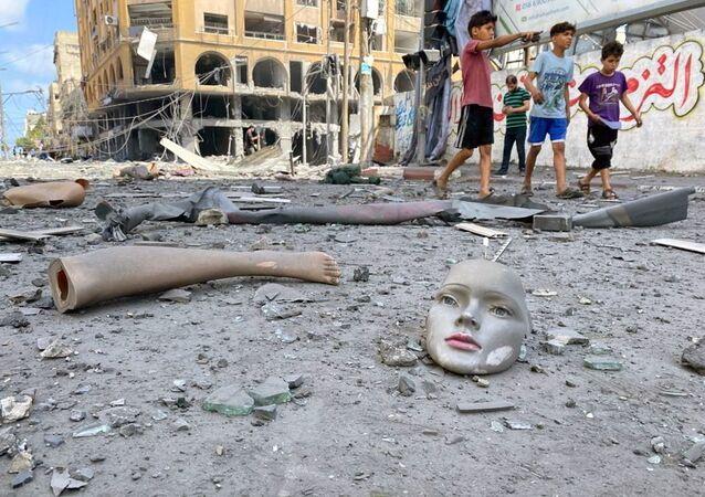 Gazze'de İsrail'in hava saldırılarında zarar gören bir binanın yakınlarında yola savrulmuş cansız manken parçaları