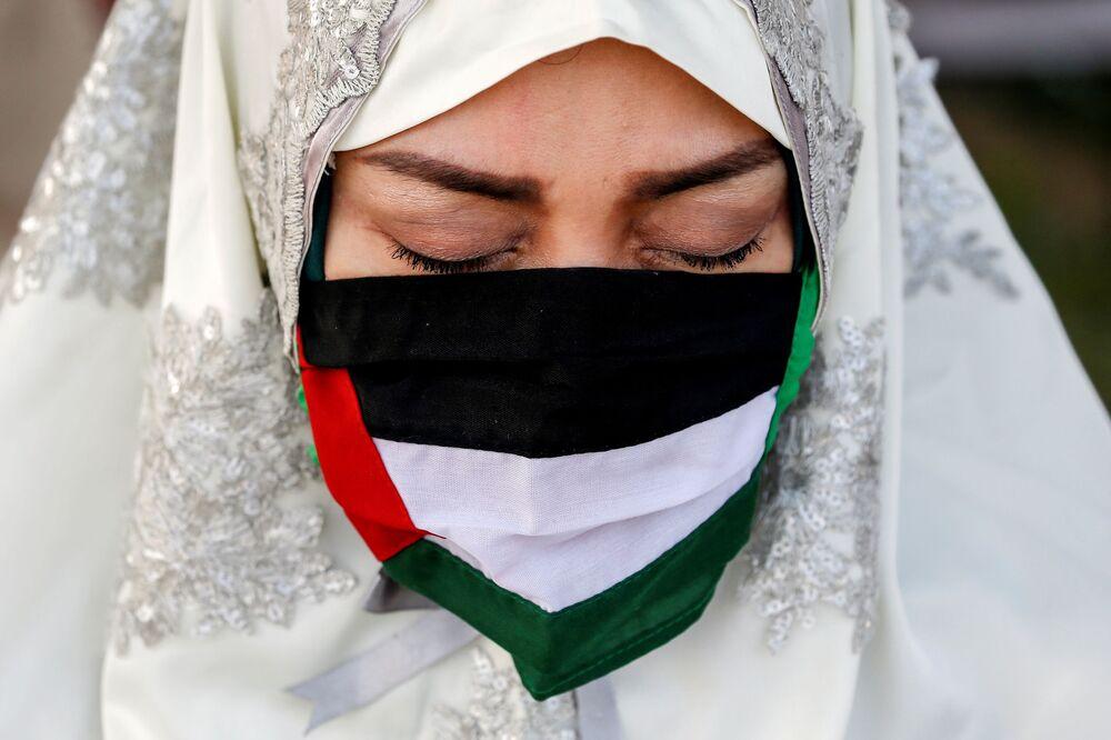 Endonezya'nın başkenti Cakarta'da Ramazan Bayramı namazına katılan Filistin bayraklı maske takan Müslüman kadın.